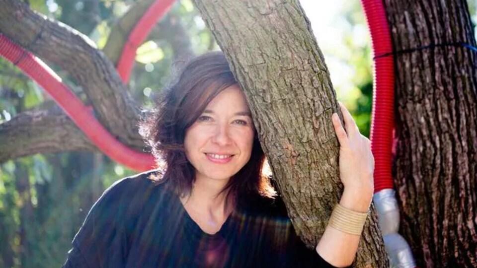 Nadine Agosti pose près d'un arbre.