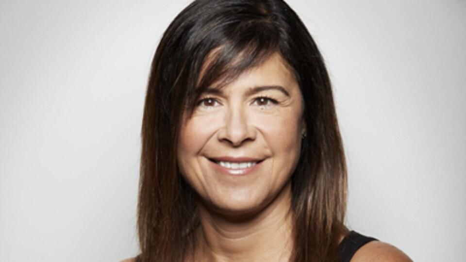 Une femme au cheveux brun sourit à la caméra devant un fond blanc.