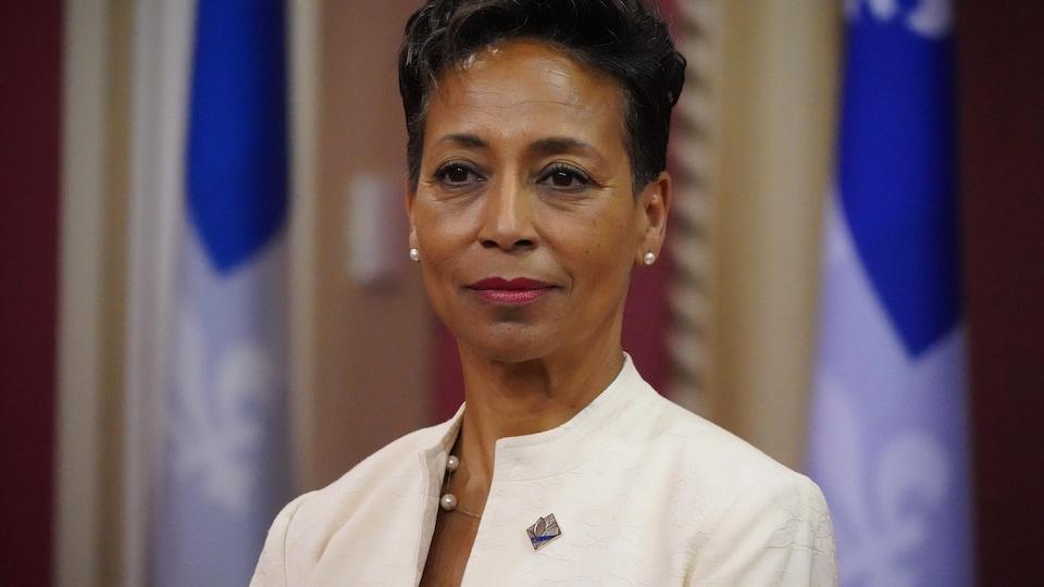 Mme Girault devant des drapeaux du Québec.