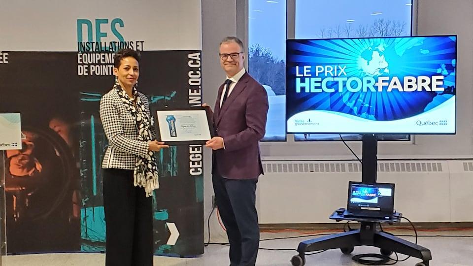 Nadine Girault et Pierre Bédard tiennent un certificat encadré.
