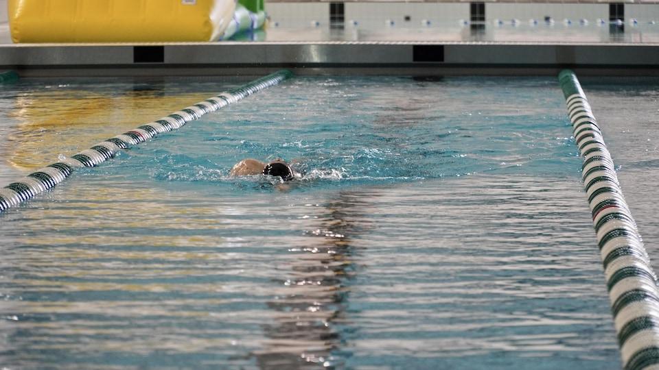 Un nageur à l'entraînement dans un corridor de natation.