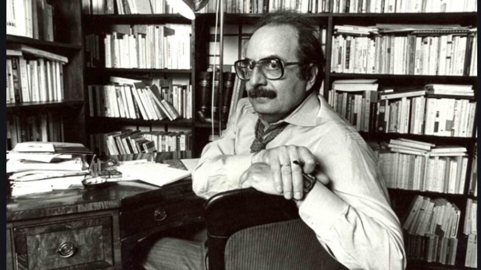 Naïm Kattan, assis sur une chaise devant une bibliothèque.