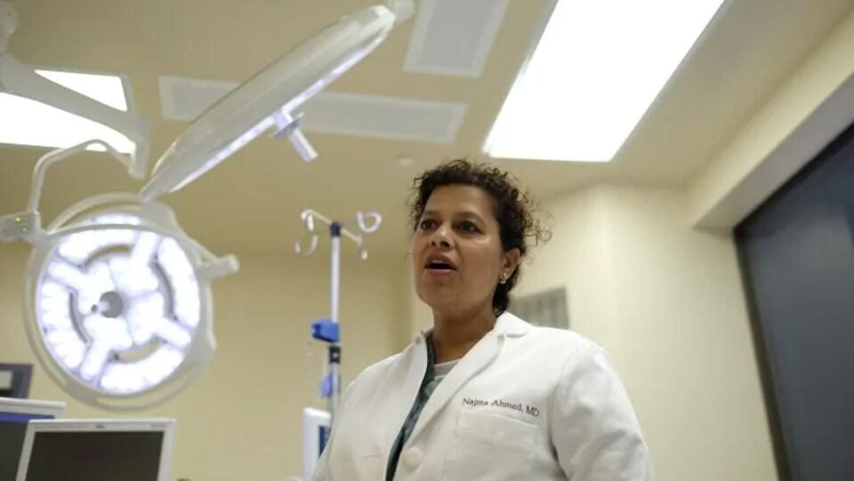 La Dre Najma Ahmed en blouse de médecin dans une salle de consultation.