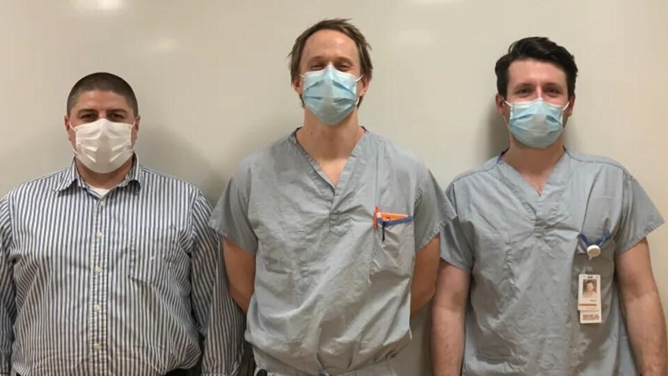 Trois hommes en sareau et avec un masque