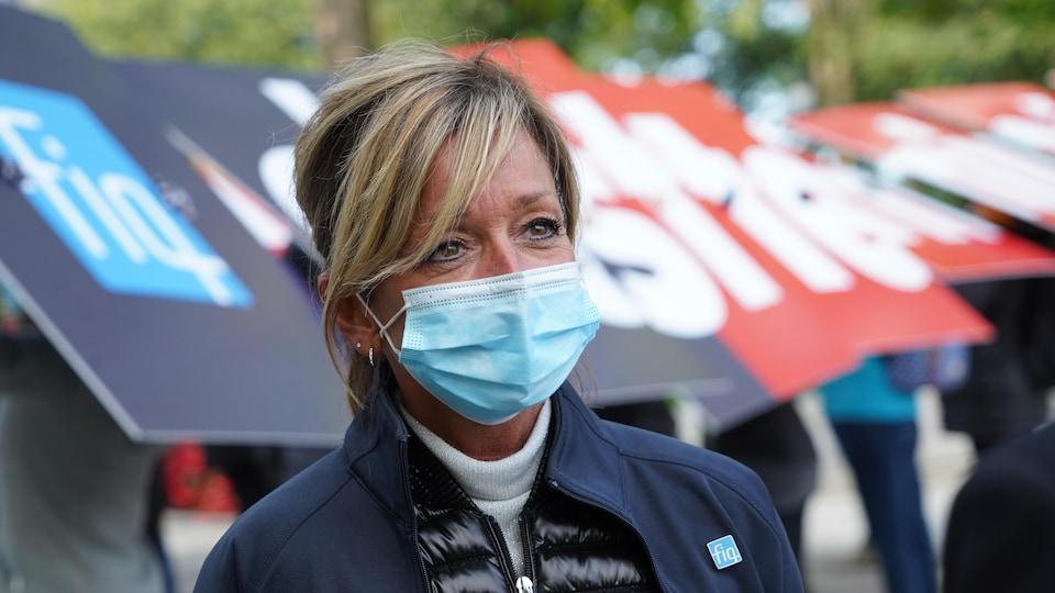 La présidente de la FIQ, portant un masque.
