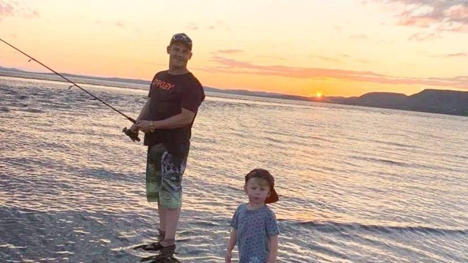 Le fils est en train de pêcher les pieds dans l'eau, au coucher du soleil.