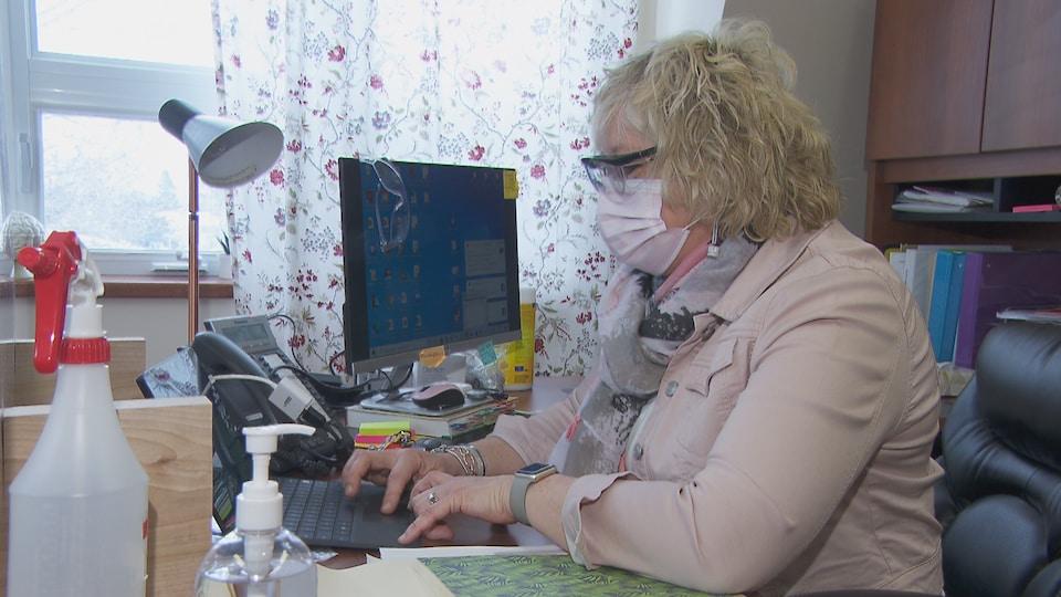 Une femme porte le masque et écrit sur son ordinateur portable.