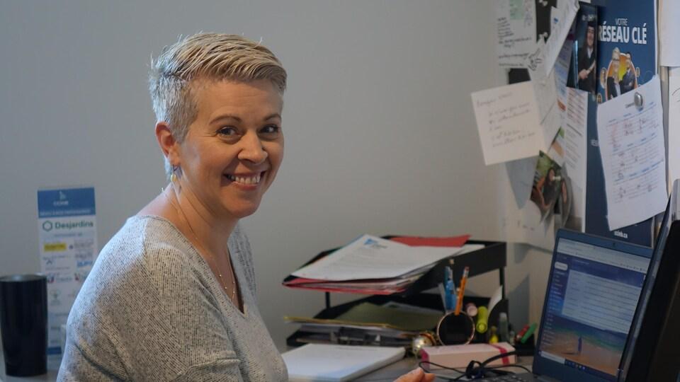 Nancy Labbé assise à son bureau d'ordinateur.