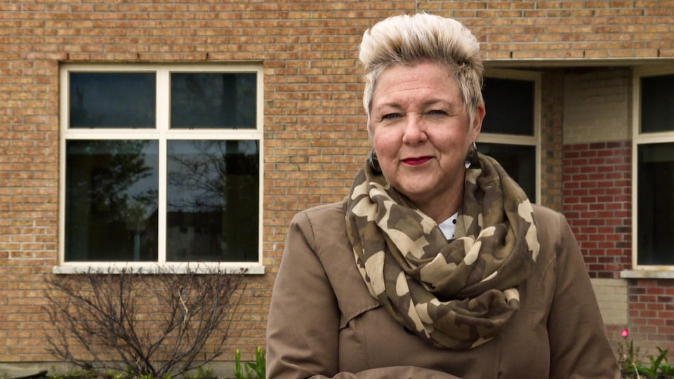 Mme Lamothe sourit devant un mur de briques.