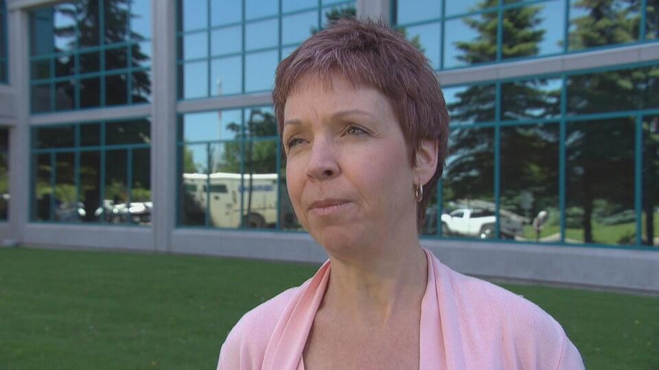 Nancy Langdon qui répond aux questions d'un journaliste devant les bureaux de Santé publique Ottawa.