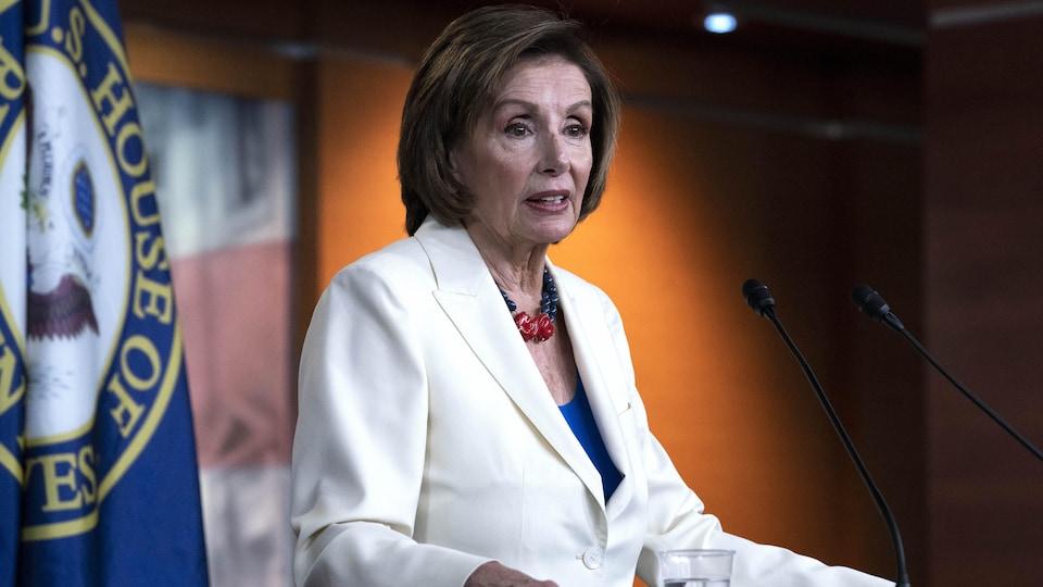 Nancy Pelosi est debout et écoute.
