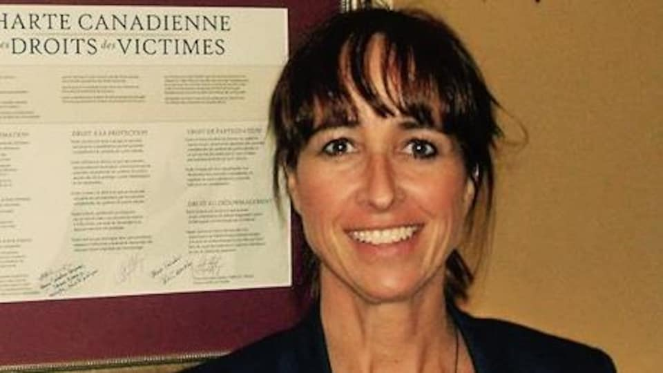 Une femme aux cheveux bruns qui pose devant une reproduction de la Charte canadienne des droits des victimes.