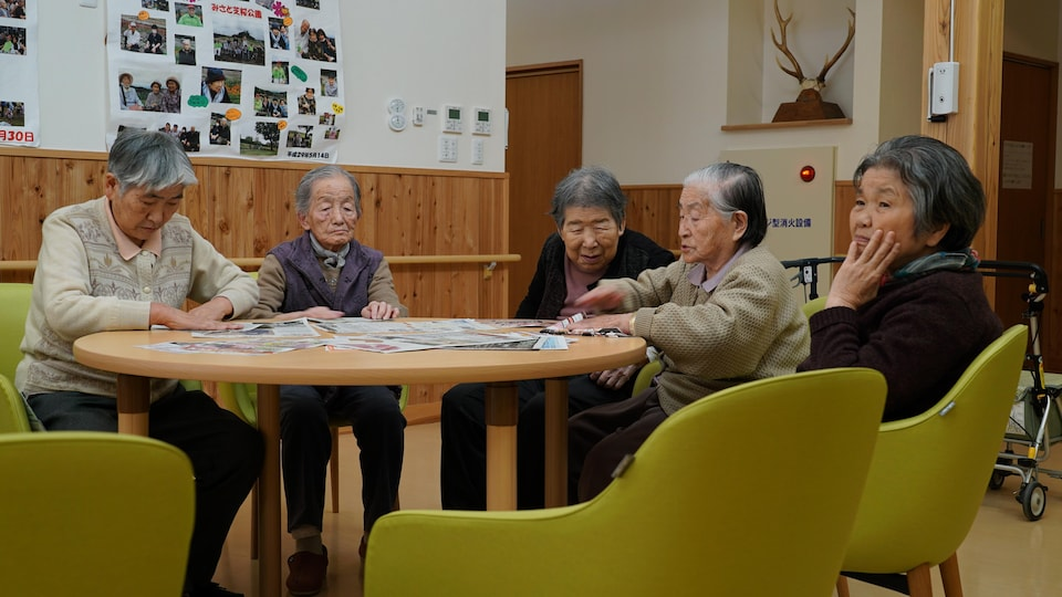 Des résidentes d'un foyer pour personnes âgées de Nanmoku au Japon regardent des circulaires de papier.