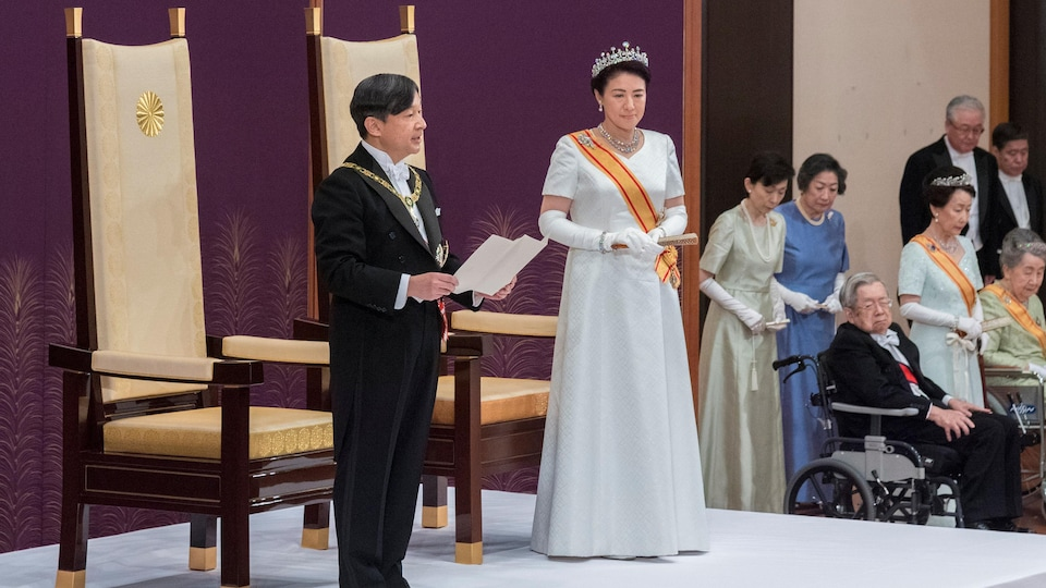 Un homme, accompagné d'une femme sur un podium, lit un texte.