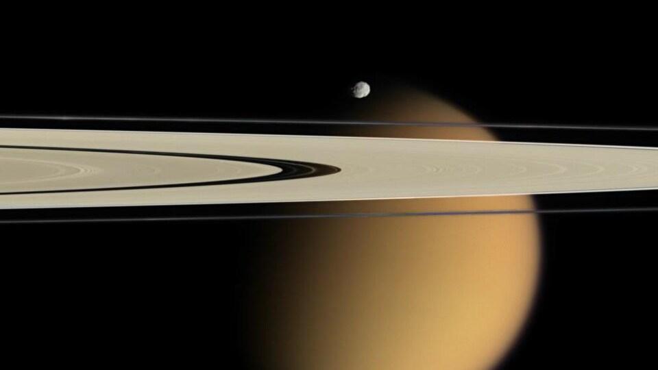 Photo captée par la sonde Cassini montrant les anneaux de Saturne, avec en arrière-plan la lune Titan. On aperçoit également la petite lune Épiméthée.
