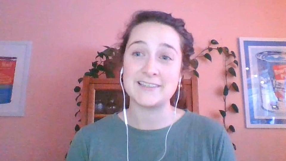 Une femme en entrevue par webcam devant un mur rose, des plantes vertes autour d'elle.