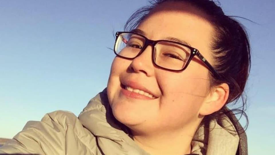 Une jeune femme autochtone sourit en étant à l'extérieur.