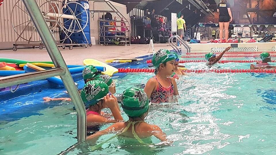 Huit enfants sont dans une piscine.