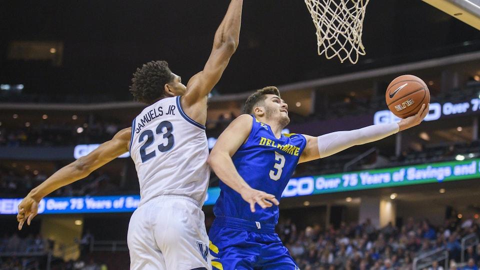 Nate Darling lève le ballon vers le panier dans un match de basketball.