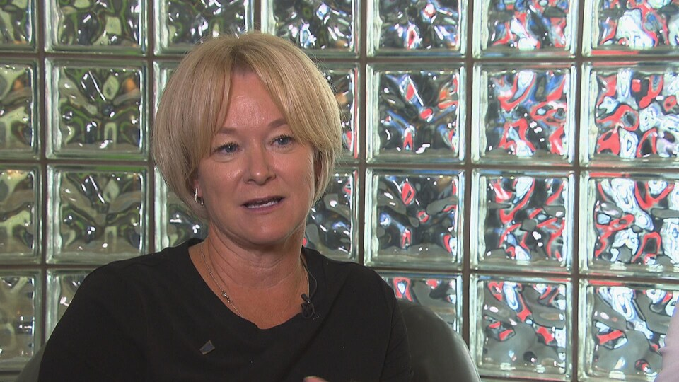 Une femme aux cheveux blonds en entrevue à la télé.
