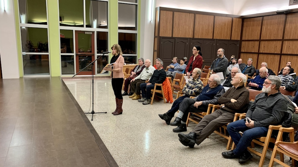 Une femme au micro devant une assemblée assise.