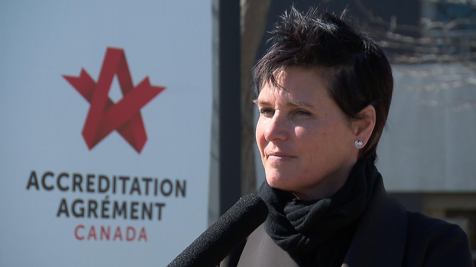 Nathalie Côté avec un foulard noir et un manteau foncé. Elle parle devant un micro.
