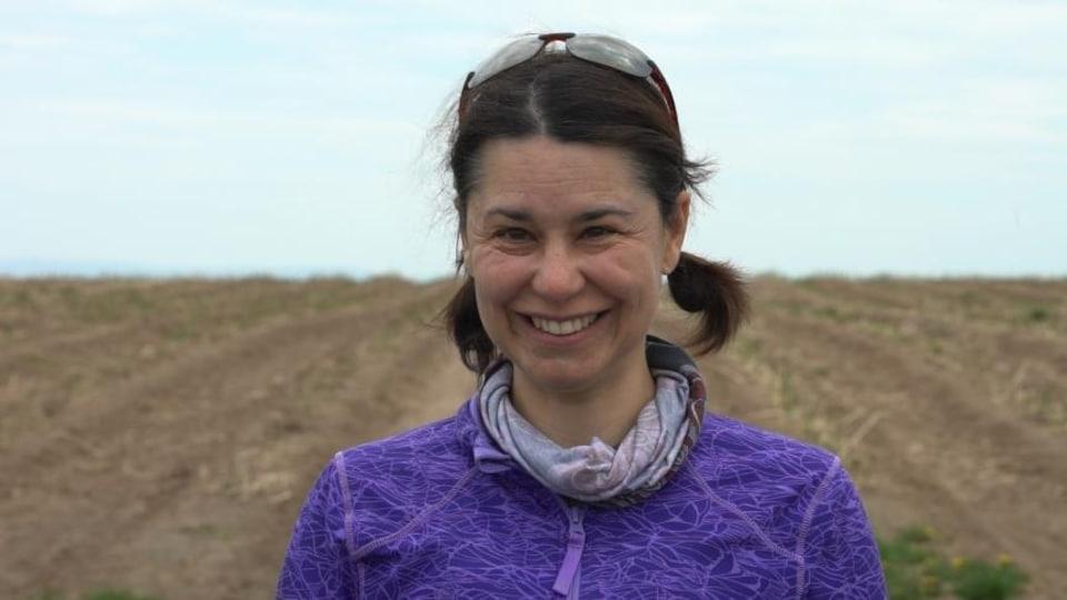 Une femme souriante devant un champ