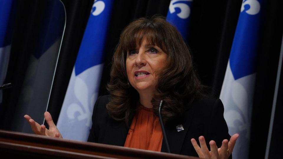 Nathalie Roy parle assise à la table de presse. On voit trois drapeaux du Québec derrière elle.