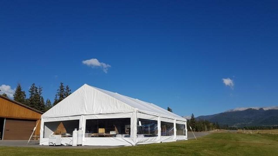 Une grande tente blanche extérieure.