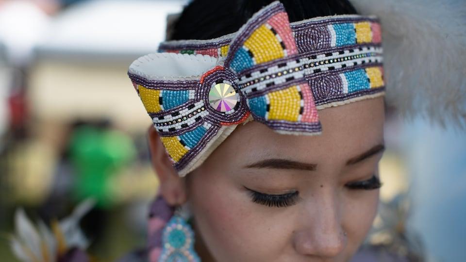 Une femme porte un bandeau décoratif.