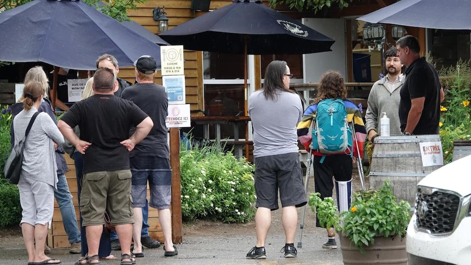 Des gens de dos attendent devant un restaurant.