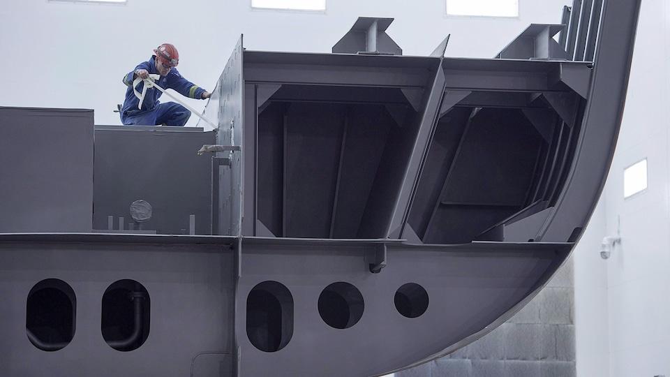 Un employé travaille sur une section d'un futur navire.