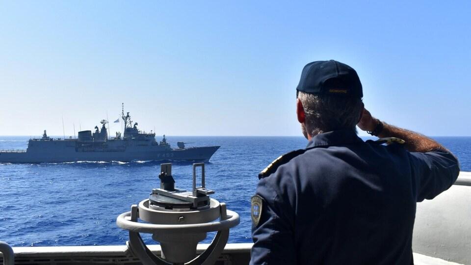 Un marin regarde un bateau de guerre au loin.