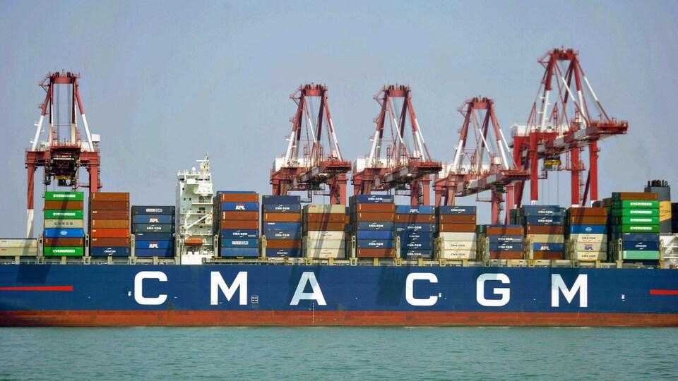 On charge et décharge des conteneurs d'un navire.