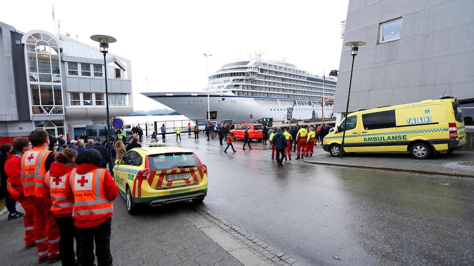Les secours attendent les passagers à gauche de l'image. Au second plan, le bateau, et sa proue pointue, se dessinent.