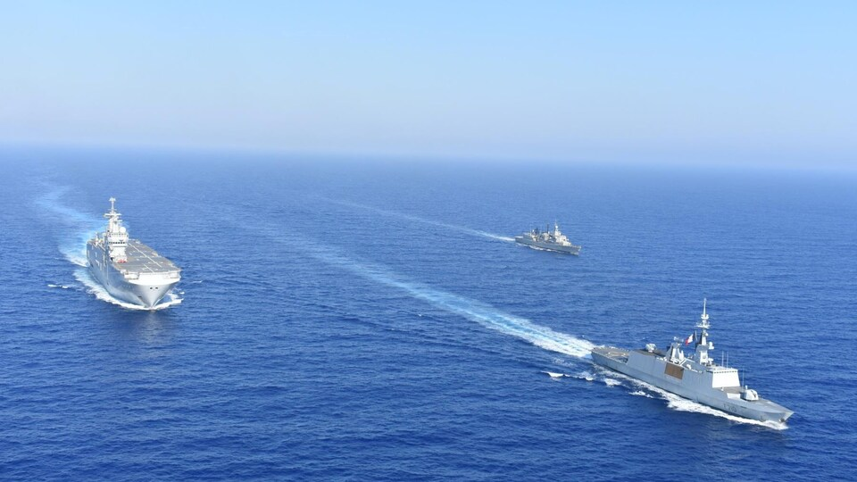 Des navires de guerre font des manœuvres en mer.