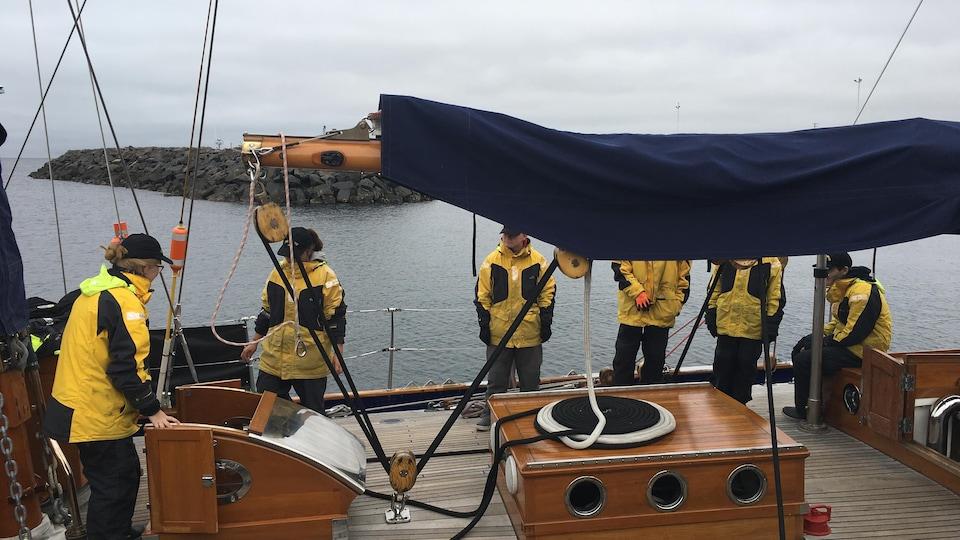 Les marins portent tous un manteau jaune et noir, ainsi qu'une casquette et des pantalons noirs.