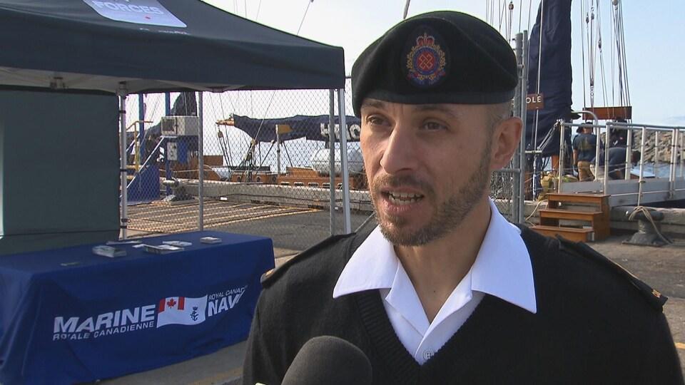 Remi Lebreux accorde une entrevue à Radio-Canada avec derrière lui son kiosque sur le quai et le voilier amarré à proximité.