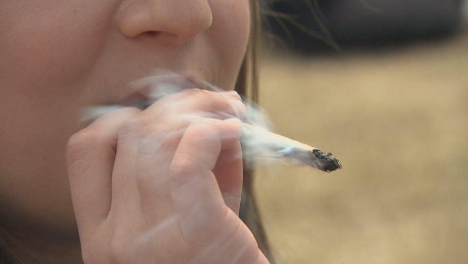 Une jeune femme blonde fume un joint de cannabis.