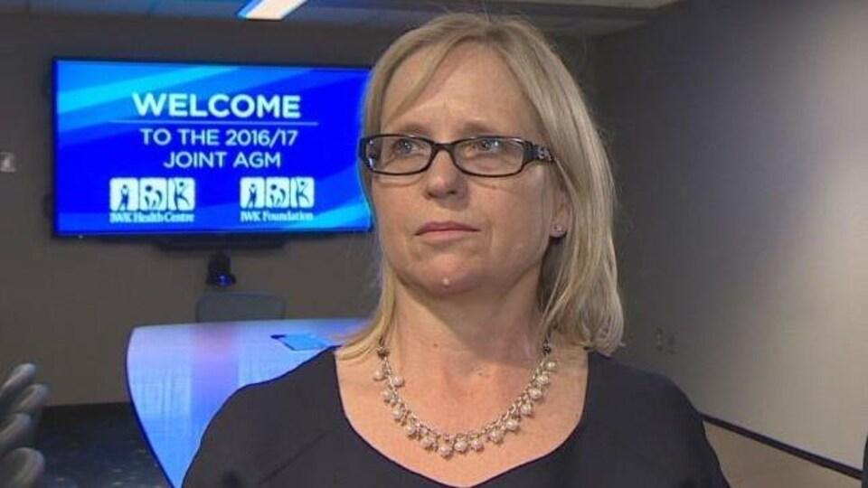 Tracy Kitch pose un écran de télévision bleu dans une salle de réunion.