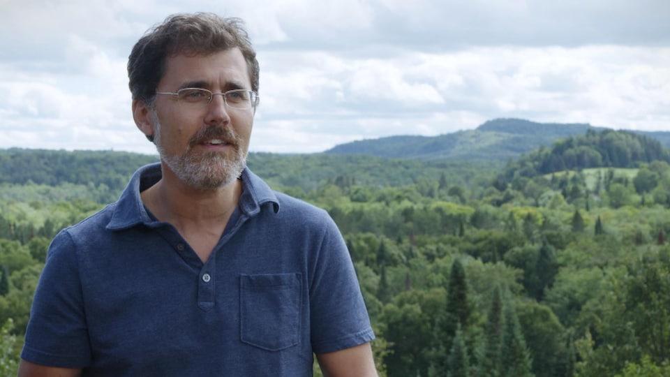 Pierre-Olivier Pineau devant un paysage de montagnes et de forêts.