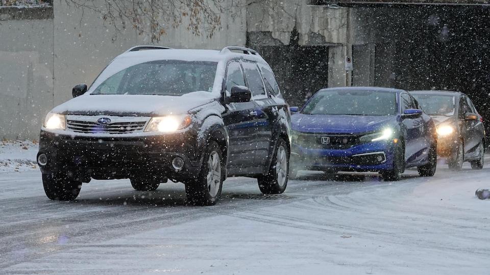 Des automobilistes alignés sur une rue enneigée.