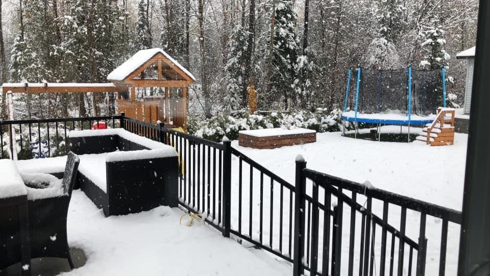 Quelques centimètres de neige sur le terrain à l'arrière d'une résidence.