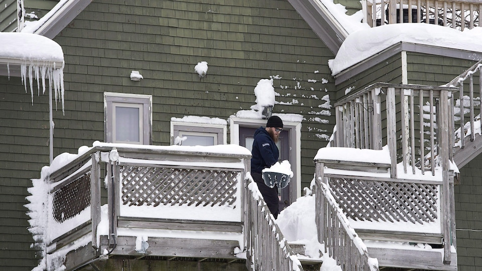 Un homme déneige son balcon et ses escaliers à Dartmouth en Nouvelle-Écosse le 14 février 2017.