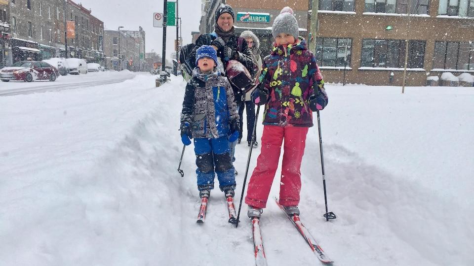 Des enfants font du ski de fonds sur le trottoir.