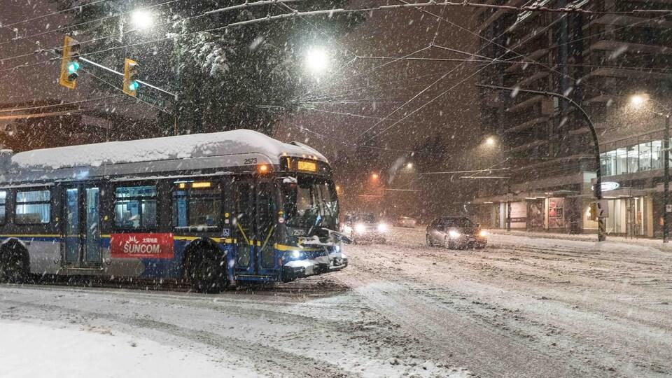 Un autobus tourne un coin de rue enneigée.