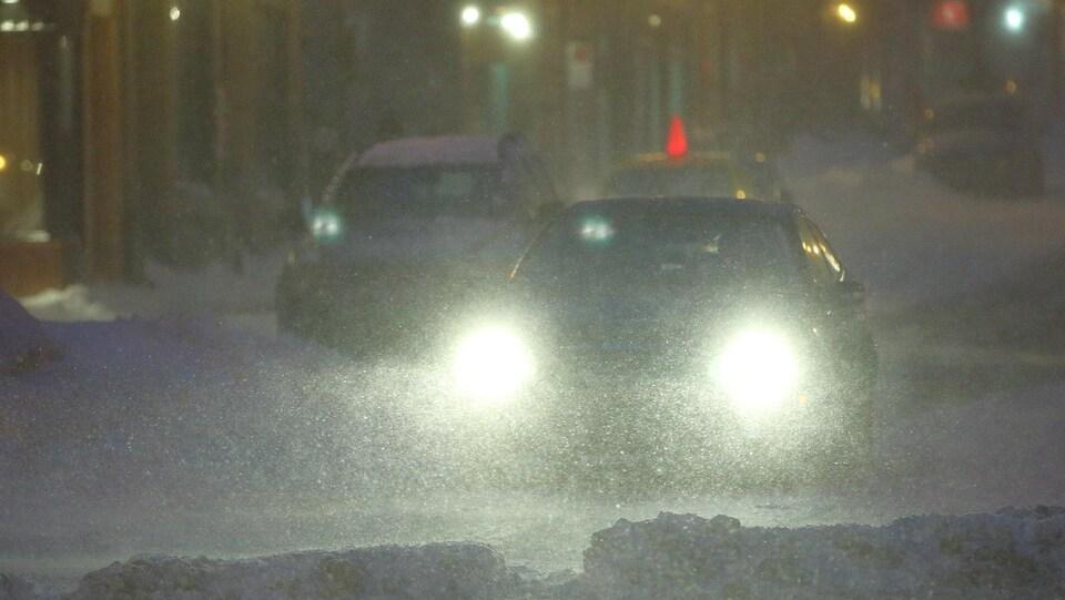 Une auto circule dans les rues de Québec, un soir de tempête.
