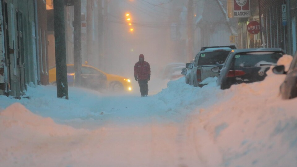 Un piéton dans une rue enneigée, à Québec.