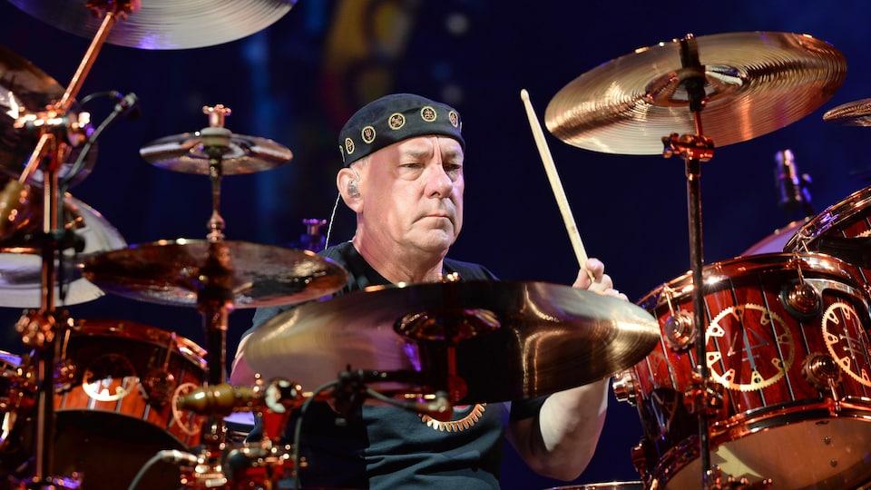 Un homme joue de la batterie.
