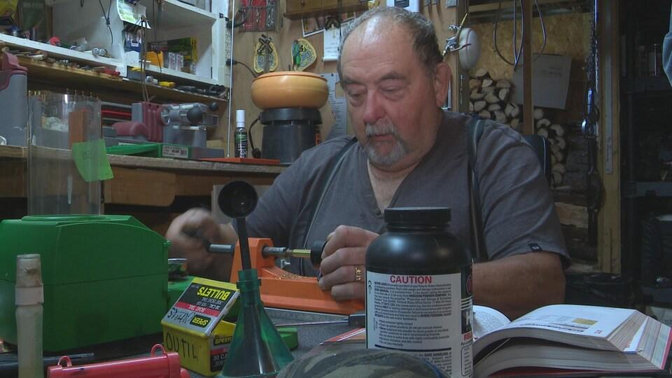 Un homme fabrique ses propres cartouches d'arme à feu pour la chasse.